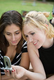 Friends on Cell Phone together (Beautiful Young Blonde and Brune Stock Photography