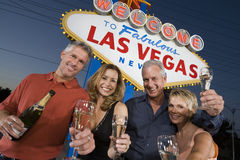Friends With Champagne Against 'Welcome To Las Vegas' Sign Royalty Free Stock Photography