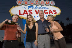 Friends With Champagne Against 'Welcome To Las Vegas' Sign Stock Image