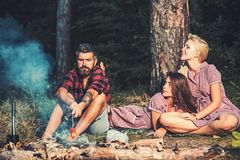 Friends camping in forest. Two playful girls in vintage dresses looking at lumberjack. Guy with serious look sitting by. Friends chaving picnic in forest. Two stock photography