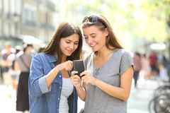 Friends checking smart phone content in the street royalty free stock image