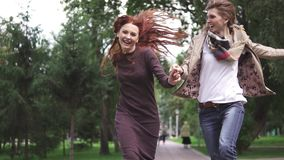 Friends cheerfully run through the summer park and hold hands. Two red girlfriends jumping, having fun and fooling. Red-haired girlfriends are walking in the stock video