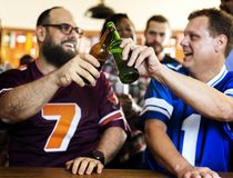 Friends cheering sport at bar together Royalty Free Stock Photography