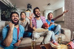 Friends cheering sport league together on tv and celebrating victory at home. Friendship, sports and entertainment concept stock image