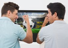 Friends cheering while watching soccer match on television Stock Image