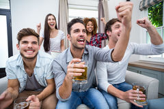 Friends cheering while watching soccer match on TV. Friends cheering and drinking alcohol while watching soccer match on TV royalty free stock photos