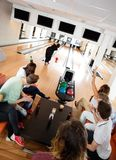 Friends Cheering Woman Bowling in Club Royalty Free Stock Photography