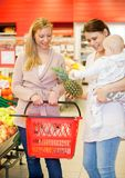 Friends with Child. Two friends buying groceries, one with a child Stock Photography