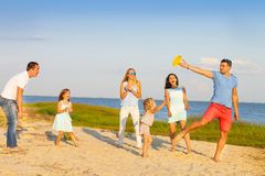 Friends with children playing with frisbee on the beach Royalty Free Stock Photos