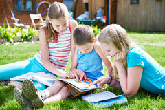 Friends children reading book outdoori on grass Royalty Free Stock Photo