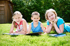 Friends children reading book outdoori on grass Royalty Free Stock Photos
