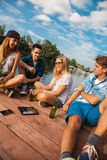 Friends Chilling Having Fun Near Lake. Group Of Cheerful Friends Having Fun Near Lake royalty free stock images