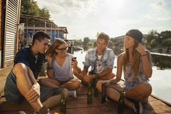 Friends Chilling Having Fun Near Lake. Group Of Cheerful Friends Having Fun Near Lake Using Smart Phone stock images