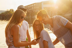 Friends Chilling Having Fun Near Lake. Group Of Cheerful Friends Having Fun Near Lake Using Smart Phone stock image