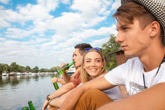 Friends Chilling Near Lake. Group Of Cheerful Friends Chilling Near Lake royalty free stock photos