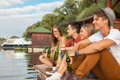 Friends Chilling Near Lake. Group Of Cheerful Friends Chilling Near Lake royalty free stock photography