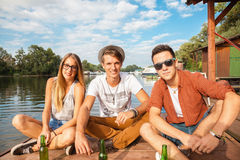Friends Chilling Near Lake. Group Of Cheerful Friends Chilling Near Lake stock images