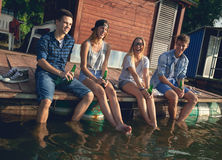 Friends Chilling Near Lake Stock Images