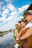 Friends Chilling Near Lake. Group Of Cheerful Friends Chilling Near Lake And Drinking Beer stock photography