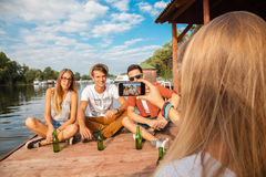 Friends Chilling Near Lake. Group Of Cheerful Friends Near Lake Taking Photo stock photography