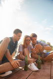 Friends Chilling Near Lake. Group Of Cheerful Friends Chilling Near Lake Using Smart Phone stock images