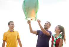 Friends with chinese sky lanterns on the beach. Summer, holidays, vacation, happy people concept - group of friends with chinese sky lanterns on the beach Royalty Free Stock Photography