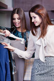 Friends are choosing a dress. Friends are choosing an appropriate dress at the shopping center Royalty Free Stock Photography