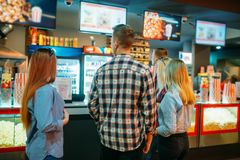Friends choosing food in cinema bar. Before the screening, back view. Male and female youth in movie theater stock photo