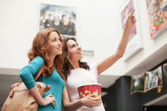 Friends choosing movie at the cinema. Beautiful young female friends choosing movie to see at the cinema Royalty Free Stock Photo