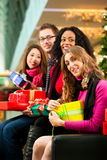 Friends Christmas shopping with presents in mall Royalty Free Stock Photos