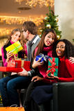 Friends Christmas shopping with presents in mall Stock Photography