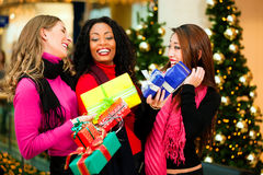 Friends Christmas shopping with presents in mall Stock Photo
