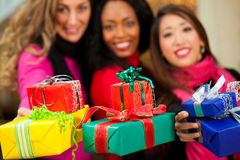 Friends Christmas shopping with presents in mall. Group of three women - white, black and Asian - with Christmas presents in a shopping mall in front of a stock images