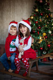 Friends on christmas - two kid, sitting on a sledge indoor, smiling Royalty Free Stock Images