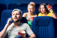 Friends in the cinema. Rude men talking with phone disturbing women on the back seats in the cinema Stock Image