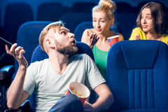 Friends in the cinema. Rude men talking with phone disturbing women on the back seats in the cinema Stock Photo
