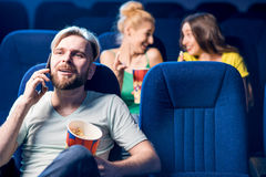 Friends in the cinema. Rude men talking with phone disturbing women on the back seats in the cinema Royalty Free Stock Photography