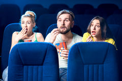 Friends in the cinema. Scared friends watching film sitting together with popcorn in the cinema Stock Photography