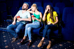 Friends in the cinema. Friends sleeping during boring film in the cinema Royalty Free Stock Images