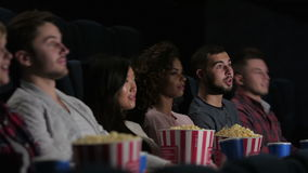 Friends in cinema watching a movie. It seems to be a funny movie. Friends in cinema watching a movie. Cinema, entertainment and people concept - happy friends stock footage