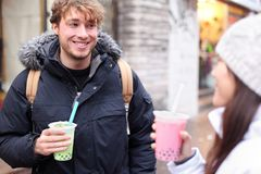 Friends in city drinking bubble tea. / pearl milk tea smiling happy and talking in chinatown of Montreal, Quebec, Canada Royalty Free Stock Images