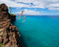 Friends cliff jumping into the ocean. Summer fun, Friends cliff jumping into the ocean Royalty Free Stock Image