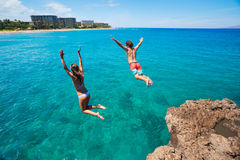 Friends cliff jumping into the ocean Royalty Free Stock Images
