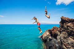 Friends cliff jumping into the ocean Royalty Free Stock Image