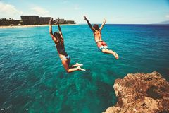 Friends cliff jumping into the ocean Stock Images