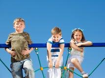 Friends climbing the net. Three school aged friends climbing the net Royalty Free Stock Image