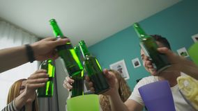Friends clink bottles at the table, bottom view stock video
