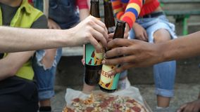 Friends clinking beer bottles relaxing outdoors, bad habit addiction, free time. Stock footage stock video footage