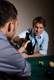 Friends clinking beer bottles at snooker table Stock Images