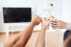 Friends clinking beer and watching tv at home Royalty Free Stock Photos